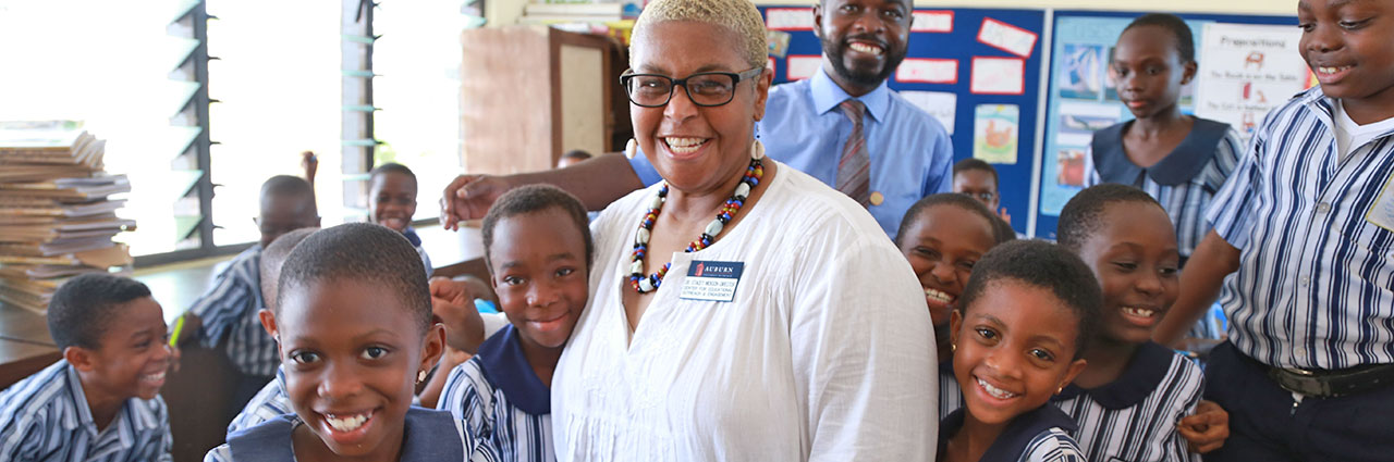 CEOE Director, Stacey Nickson poses for photo with african students in Ghana primary school.
