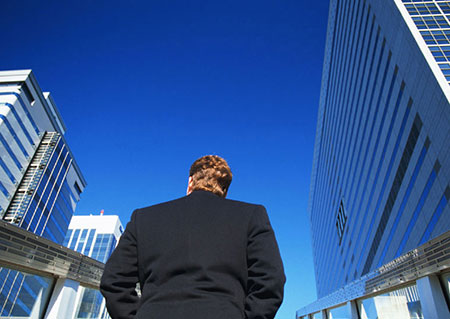 Man in business suit walking among tall buildings