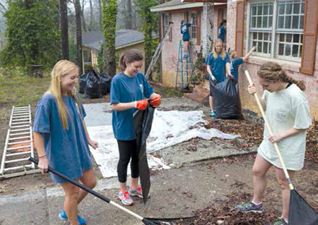 Students rake leaves during a community service project