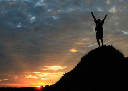 Man standing at top of hill with arms in the air signifying personal achievement