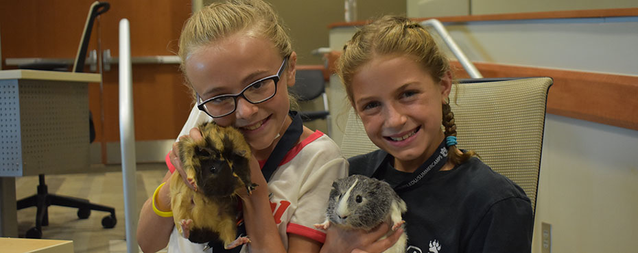 Two students hold exotic animals from the Veterinary School.