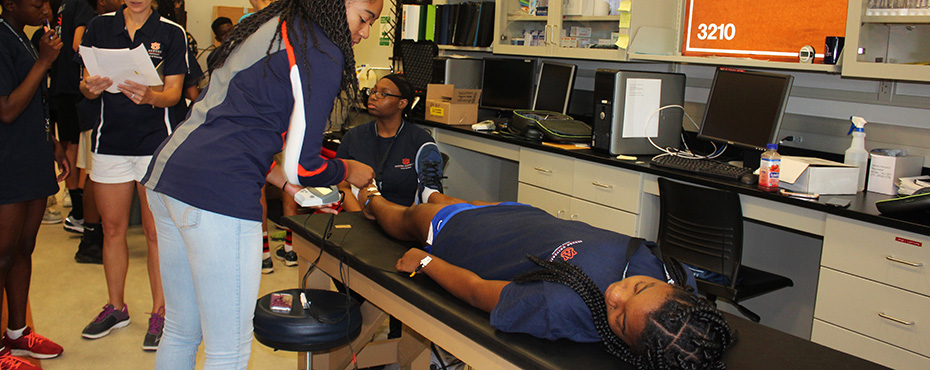 A student lays on a table to get her electrical reading from an Auburn University Kinesiology student.