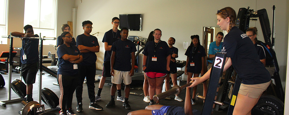 A group of students watch as another camper sees how many times she can bench press the bar.
