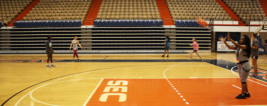 Students practice throwing the ball in pairs at the Auburn University Coliseum