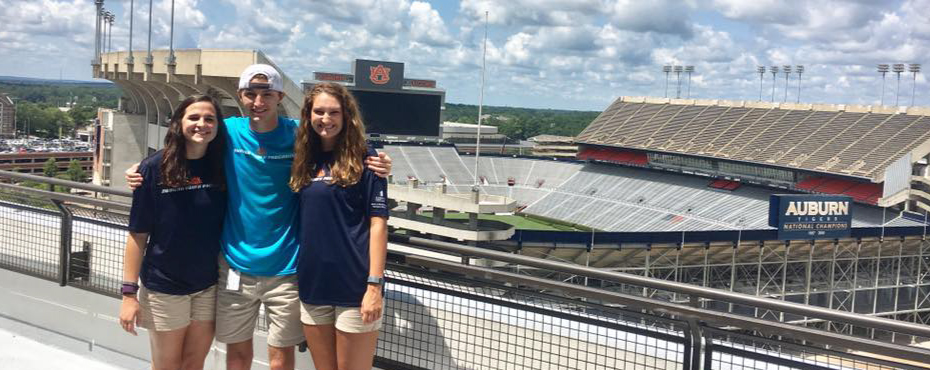 A group of Auburn Youth Program's counselors pose for the camera to show off Auburn University's football stadium in the background.