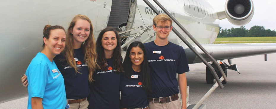A few Auburn Youth Programs staff members pose in front of a plane at Auburn University's Regional Airport.